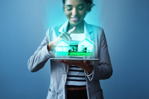 A woman holding a tablet with a 3d hologram of a home, highlighting the Canadian Real Estate Homebuying through the ibuyer program